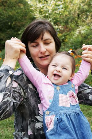 Happy mother playing with baby daughter outdoors Фото со стока