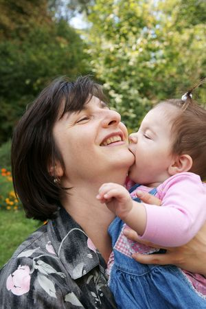 Happy baby daughter kissing mother outdoors photo