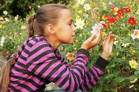 Preteen girl admiring flowers