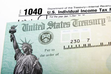 returns: Tax return check and 1040 individual income form
