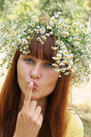 Beautiful cheerful girl in field flower garland outdoors showing secret sign