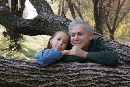 Happy father and daughter talking in autumn park