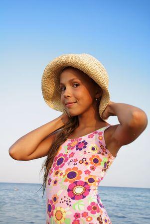 sunbath: Preteen girl in straw hat enjoying sun-bath on sea beach