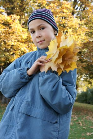 preteens girl: Preteen girl holding yellow leaves outdoors Stock Photo