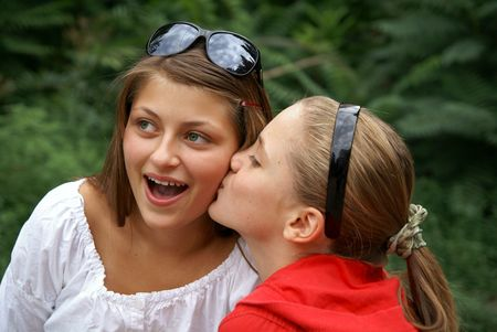 Two beautiful cheerful teenage girls kissing outdoors photo