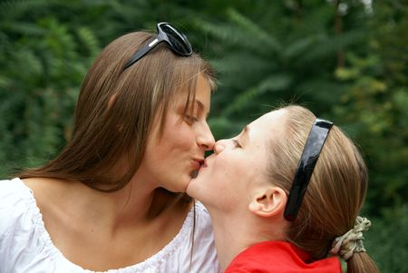 Two beautiful cheerful teenage girls kissing outdoors