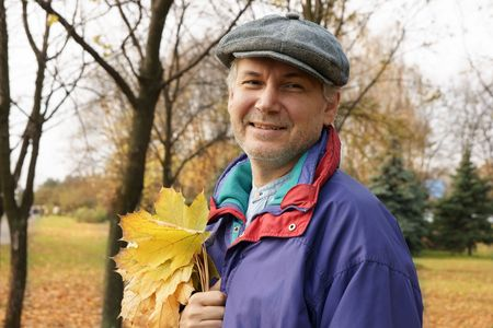 Cheerful mature man holding yellow leaves outdoors Фото со стока