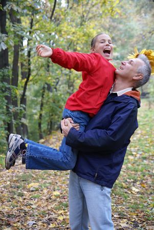 Father and daughter playing in autumn park