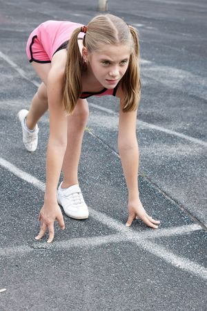 preteen girl: Preteen girl starting to run on track