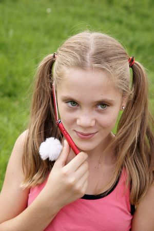 Happy teenage girl talks on cellular phone on green grass background  Фото со стока