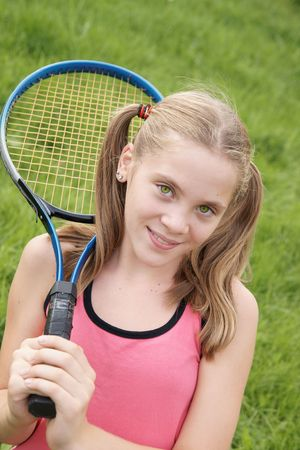 Happy teenage girl in sport outfits holding tennis racket on green grass background outdoors Фото со стока
