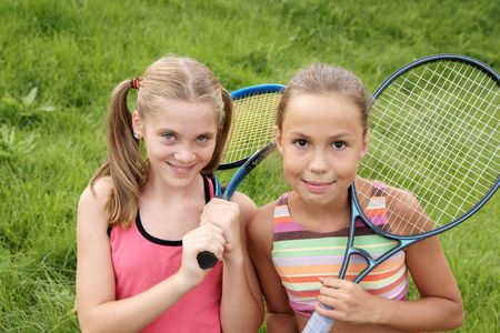 preteen girls: Happy preteen girls in sport outfits with tennis rackets on green grass background  Stock Photo
