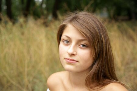 wistful: Portrait of wistful looking young woman outdoors on green grass background