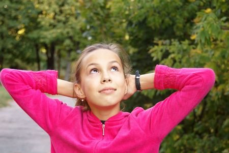 Portrait of happy preteen girl outdoors on green leaves background photo