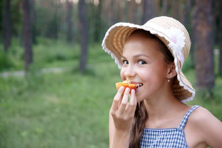 Portrait of preteen girl in straw hat eats apricot on green leaves background photo