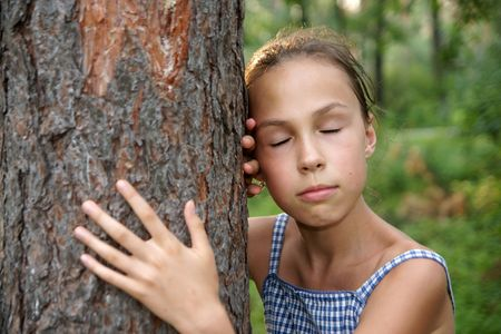 Portrait of dreaming preteen girl hugging tree trunk on green leaves background Фото со стока