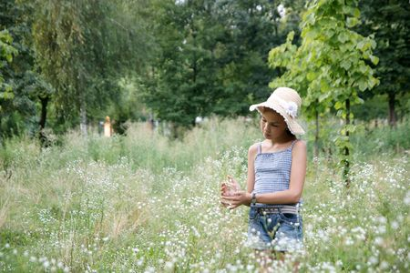 Happy preteen girl plays with flowers on meadow background