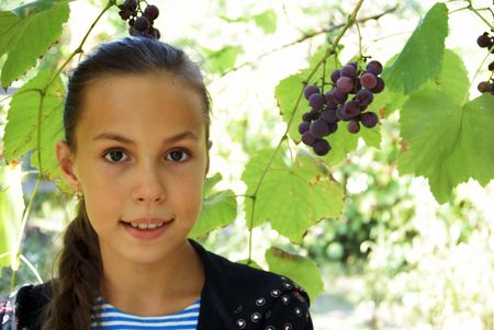 Portrait of preteen girl with grapes on green leaves background
