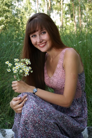 Portrait of beautiful happy young woman with field flowers outdoors