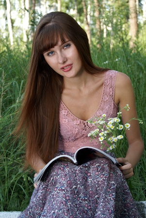 Portrait of beautiful happy young woman with magazine outdoors
