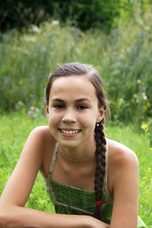 petite: Portrait of teen girl on summer meadow green grass background