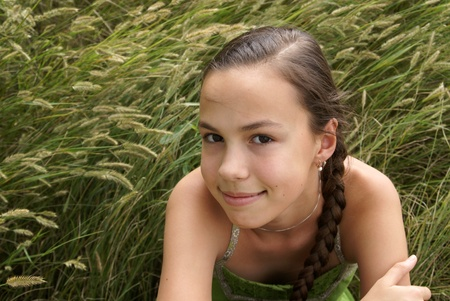 petite: Portrait of teen girl on summer meadow green grass background Stock Photo