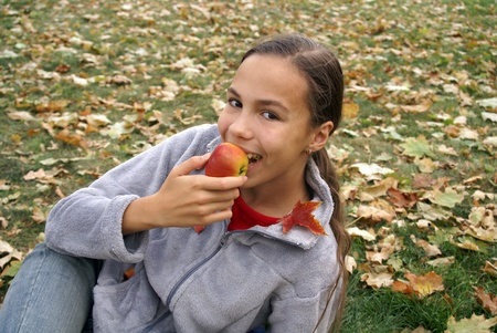 Happy teen girl eats apple on autumn leaves background outdoors Фото со стока - 10849385