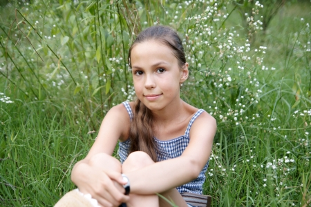 Happy preteen girl sitting on grass background