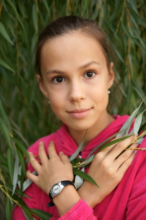 Portrait of happy preteen girl on green leaves background