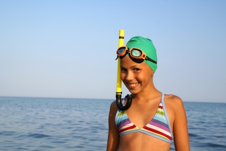 Cheerful preteen girl in diving outfit enjoying sun-bath on sea beach