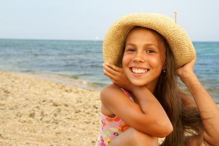 sunbath: Vrolijke preteen meisje in strooien hoed genieten van zon-bad op zee strand