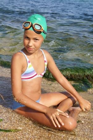 海のビーチで日光浴を楽しんでいるダイビングの衣装でプレティーン ヌード少女