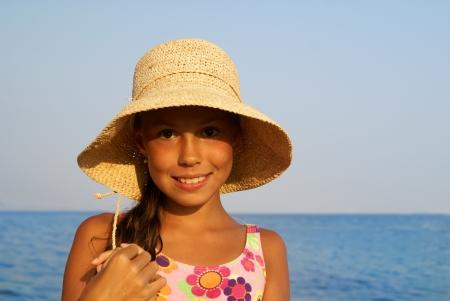 sunbath: Vrolijke preteen meisje in stro hoed genieten van zon-bad op zee strand