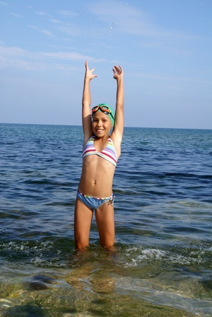 Preteen girl in diving outfit playing with water on sea beach
