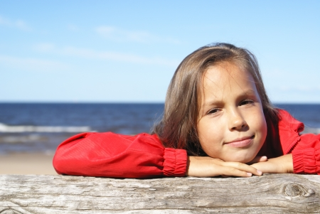 Preteen girl in red on a beach photo