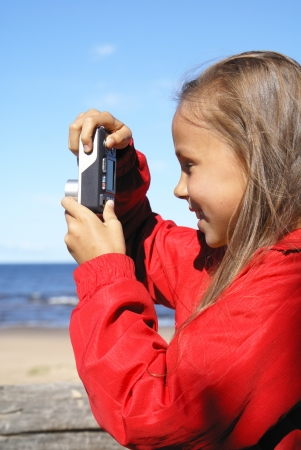 Preteen girl taking pictures on a beach photo