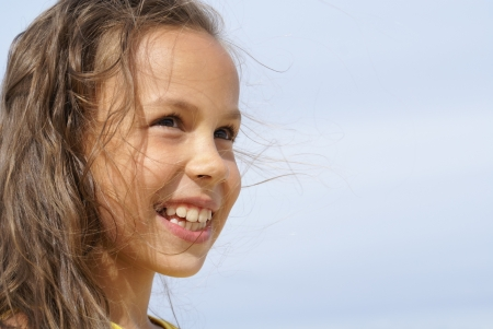 Cheerful peteen girl on blue sky background