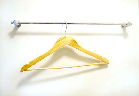closet rod: Wooden clothes hanger suspended from metal rod, isolated