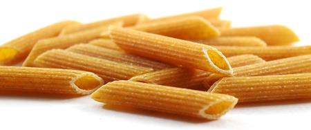 ridged: Heap of ridged organic whole wheat penne pasta - isolated