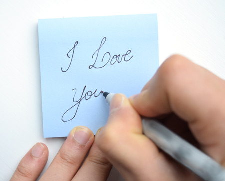 i pad: Hand writing I love you! with a heart on a sticky note pad Stock Photo