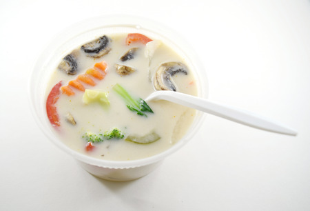 bok choy: Thai tom kha gai (chicken coconut soup) in plastic takeout container with spoon - isolated
