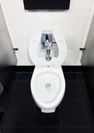 loo: White toilet in workplace office bathroom on black tile floor