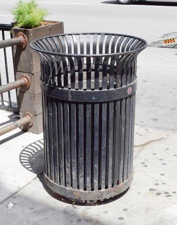 discard: Black public trash can on city street Stock Photo