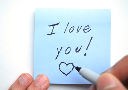 Hand writing I love you! with a heart on a sticky note pad Stock Photo