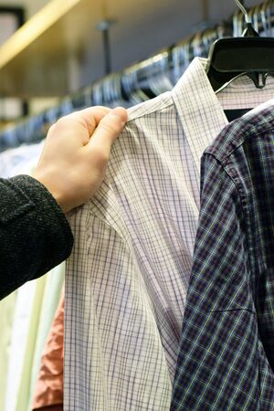 button down shirt: Male hand pulling checkered button down shirt off clothing rack in store