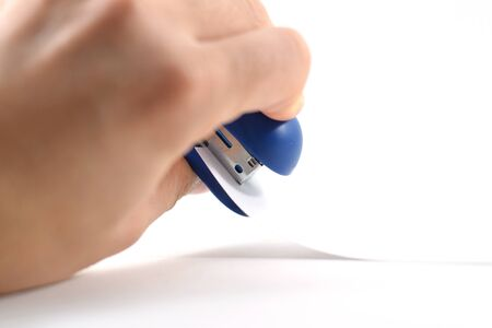 stapled: Hand stapling papers with a blue mini stapler - isolated