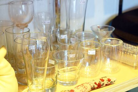 consignment: Used glasses and cups for sale with price tag at a second hand store