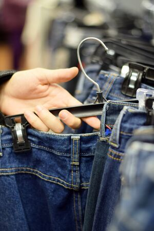 Male hand looking through pants on a clothing rack in store