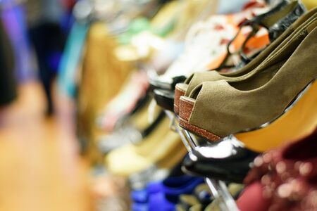 consignment: Rows of stylish womens shoes and high heels on a rack for sale at a clothing store