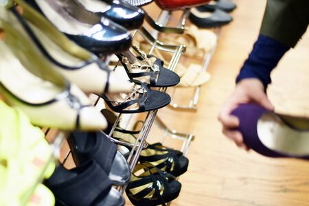 consignment: Hand shopping for shoes on a rack in clothing store Stock Photo